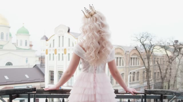 Beautiful young sexy woman stands on balcony posing backdrop winter spring old cityscape. Princess blonde cute face elegant dress. wellness white long flowing curly wavy hair. Natural makeup pink lips