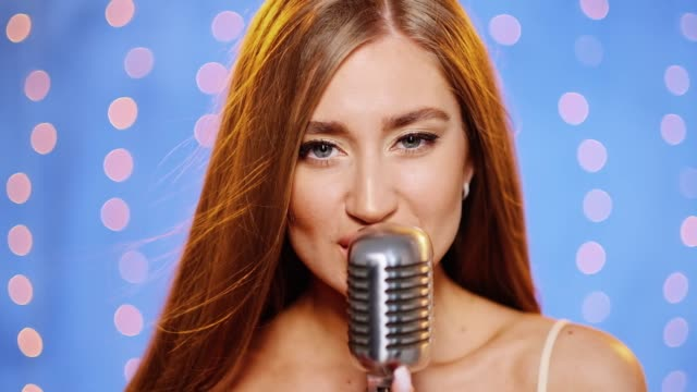 A beautiful young sexy woman with long hair in an evening dress with sequins. Girl sings on stage in a vintage microphone, dances and smiles.