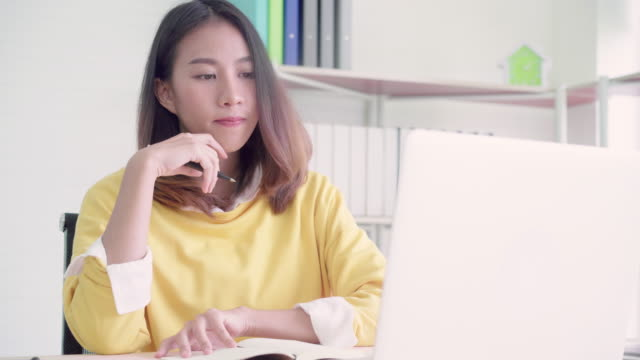 Beautiful young smiling asian woman working laptop on desk in living room at home. Asia business woman writing notebook document finance and calculator in home office. Enjoying time at home concept.