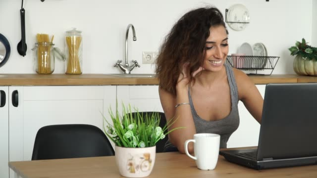schöne junge lächelnde brünette frau sitzt am tisch mit laptop und trinken kaffee in der küche zu hause - freischaffender stock-videos und b-roll-filmmaterial