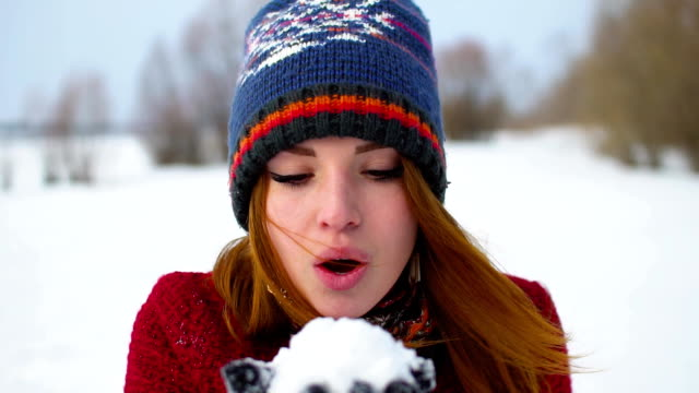 Beautiful Young Smiling Winter Girl Blowing Snow On Field in super slow motion 120fps video