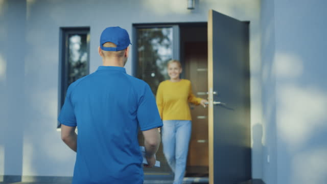 beautiful young smiling woman opens doors of her house and meets pizza delivery guy who gives her cardboard boxes full of tasty steamy pizza. back view following shot - food delivery filmów i materiałów b-roll