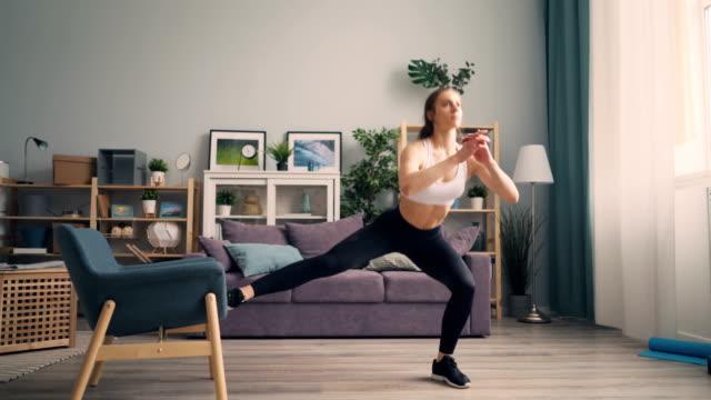 vídeos de stock e filmes b-roll de beautiful young sportswoman doing squats at home using armchair training body - agachar se