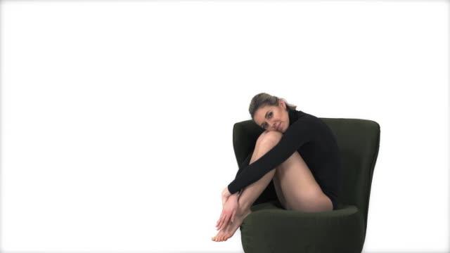 vacker ung idrottskvinna sitter i fåtöljen barfota, ben korsade, drömmer eller tänker - gympingdräkt bildbanksvideor och videomaterial från bakom kulisserna