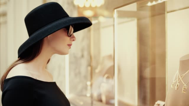 A beautiful young stylish lady in a hat and sunglasses approaches the shop window of a boutique and looks at goods with interest. Luxury jewelry store