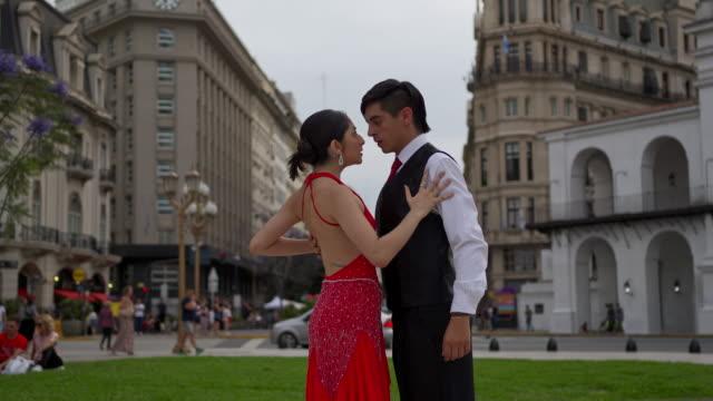 町の広場で踊る美しい若いタンゴダンスのカップル ビデオ