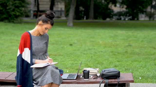 Beautiful young teen girl student is writing in notebook at outdoor park.
