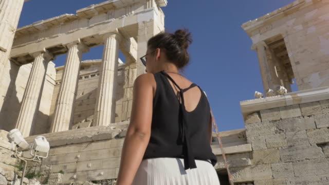 stockvideo's en b-roll-footage met mooie jonge toeristische vrouw lopen onder de beroemde parthenon ruïnes in athene griekenland akropolis op een zonnige zomerdag - athens