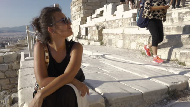 Beautiful young tourist woman walking among famous Parthenon ruins in Athens Greece Acropolis on a sunny summer day video