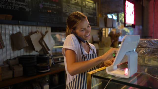 Beautiful young waitress registering a delivery on system while talking to customer on phone Beautiful young waitress registering a delivery on system while talking and laughing with customer on phone wait staff stock videos & royalty-free footage