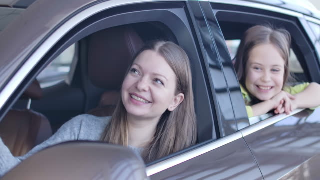 Beautiful young woman and little girl sitting in car in showroom and clapping hands. Excited mother and daughter choosing vehicle in dealership. Cinema 4k ProRes HQ.