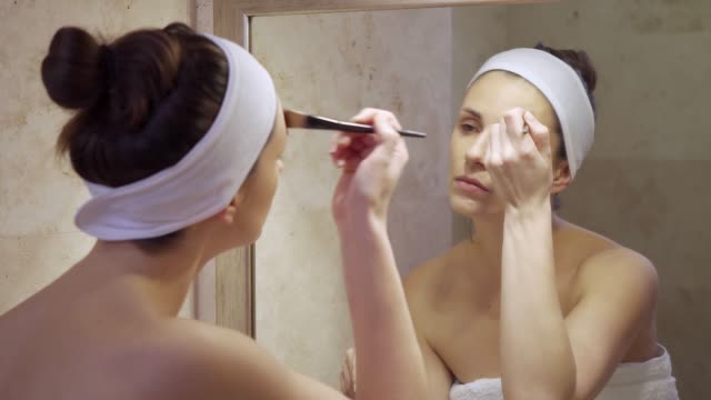 Beautiful young woman applies fluid looking in the mirror Beautiful young brunette woman applies fluid looking in the mirror in bright bathroom foundation make up stock videos & royalty-free footage