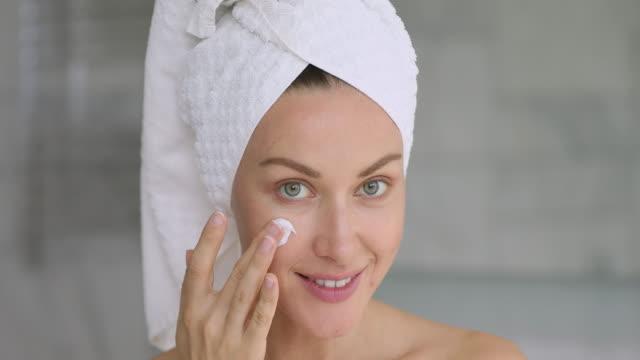 vacker ung kvinna ansöker crème på ansiktet tittar på kameran - endast en ung kvinna bildbanksvideor och videomaterial från bakom kulisserna