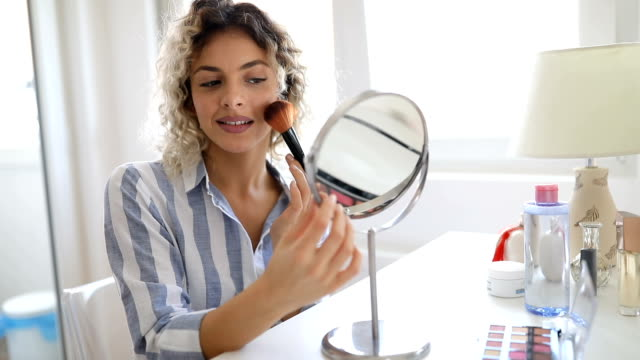vidéos et rushes de belle jeune femme appliquant composent - pinceau à maquillage