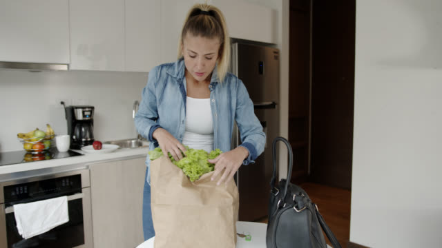 Beautiful young woman arriving home with fresh groceries in a paper bag video