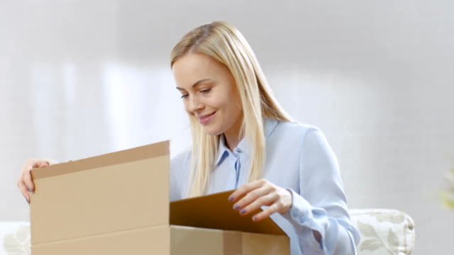 Beautiful Young Woman at Home Opens Cardboard Box while Sitting on a Couch in Her Bright Living Room. She Smiles. video