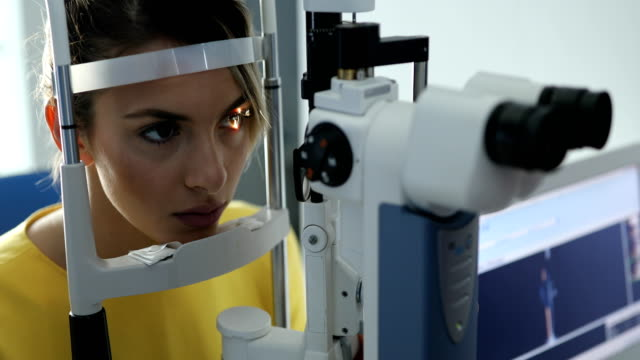 Beautiful young woman at ophthalmologist Beautiful young woman at ophthalmologist , Eyesight exam ophthalmologist stock videos & royalty-free footage