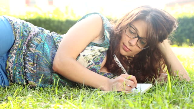 stockvideo's en b-roll-footage met beautiful young woman at park writing on notepad - werkboek