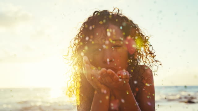 beautiful young woman blowing glitter confetti in slow motion - beach fashion stock videos and b-roll footage