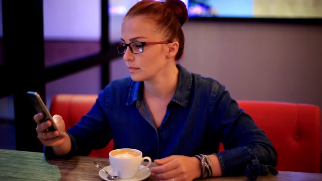 beautiful young woman businessman with red hair and glasses sitting at a table in a cafe and eating dessert. - служащая стоковые видео и кадры b-roll