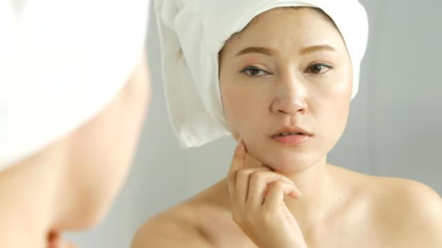 stockvideo's en b-roll-footage met mooie jonge vrouw haar gezicht in de spiegel te controleren. jonge vrouw in de spiegel in haar badkamer kijken - skincare