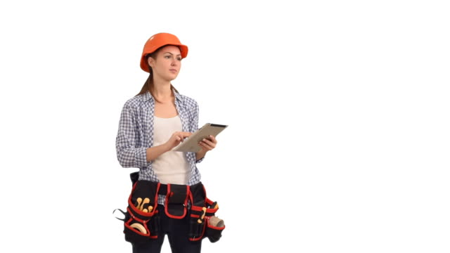 Beautiful young woman construction worker working on tablet video