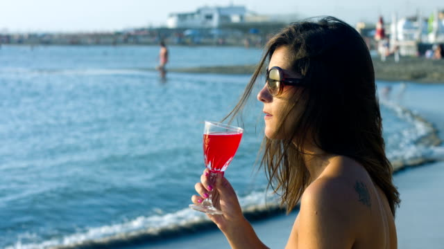 beautiful young woman drinking cocktail by the sea: sunset, wind, summer video