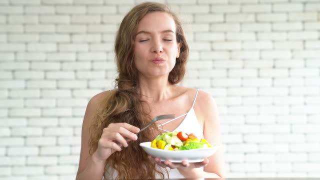 a beautiful young woman eating salad - insalata video stock e b–roll