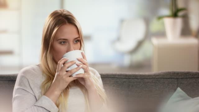 Belle jeune femme dégustant une tasse de thé tout en se reposant sur l'entraîneur - Vidéo