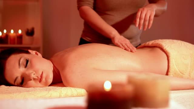 Beautiful young woman enjoying massage dolly shot video