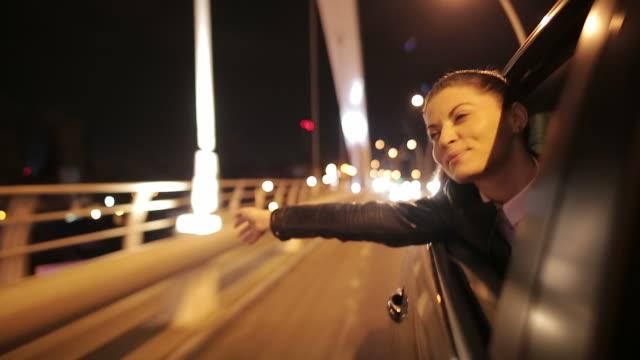 vidéos et rushes de belle jeune femme appréciant le voyage. - voiture nuit