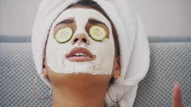 a beautiful young woman gets a face mask in the spa center, lying with cucumbers in her eyes. happy and gets a lot of fun. - cetriolo video stock e b–roll
