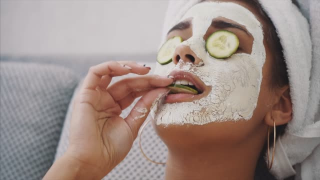 A beautiful young woman gets a face mask in the spa center, lying with cucumbers in her eyes. Happy and gets a lot of fun. A beautiful young woman gets a face mask in the spa center, lying with cucumbers in her eyes. Happy and gets a lot of fun. Smile indulgence stock videos & royalty-free footage