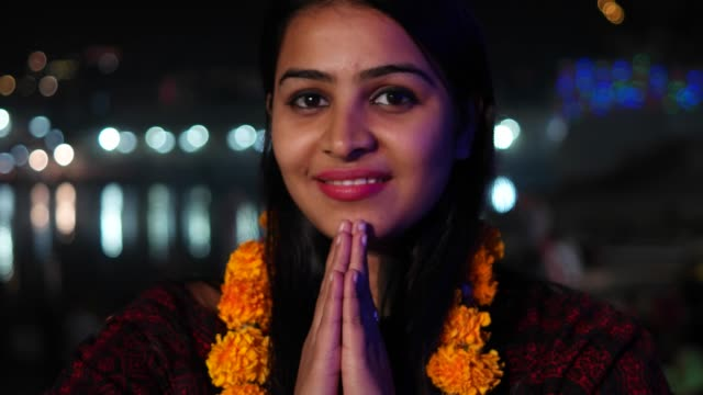 beautiful young woman hands joined in namaste greets with orange marigold flower garland on her neck offers prayers worship god goddess hands welcomes smiles glowing respect believer religion handheld - ghat filmów i materiałów b-roll