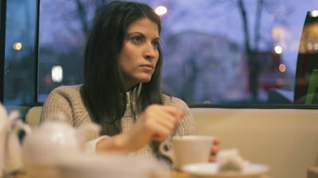vídeos de stock e filmes b-roll de bela jovem, tendo uma conversa no café. - coffee table