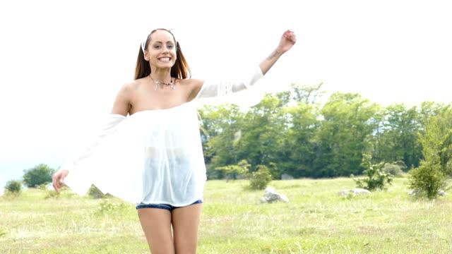Beautiful young woman having fun in grassland,slow motion video