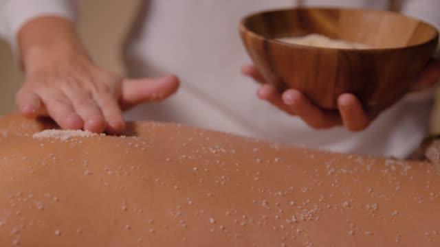 beautiful young woman having salt massage at spa - china drug video stock e b–roll