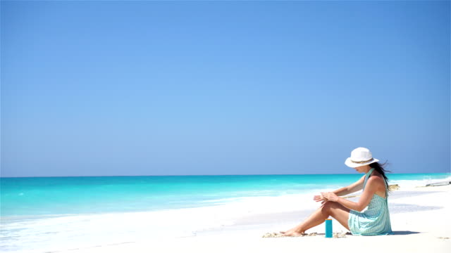 beautiful young woman holding a suncream lying on tropical beach - sun cream stock videos & royalty-free footage