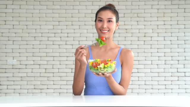 vídeos de stock e filmes b-roll de a beautiful young woman holding bowl of salad - saladeira