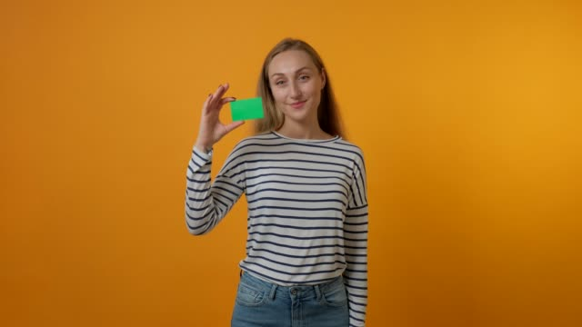 A beautiful young woman holds a blank green card in her hand. A beautiful young woman holds a blank green card in her hand. The concept of banking, credit card, business card holders. Yellow background. 4K video. business card stock videos & royalty-free footage