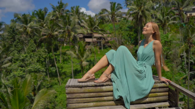 A beautiful young woman in a blue dress visits famous Tegalalang Rice Terraces in Ubud village on the Bali island A beautiful young woman in a blue dress visits famous Tegalalang Rice Terraces in Ubud village on the Bali island. one mid adult woman only stock videos & royalty-free footage