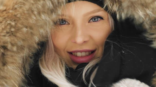 vídeos de stock, filmes e b-roll de mulher jovem e bonita em um aconchegante casaco num dia de inverno nevado - moda de inverno