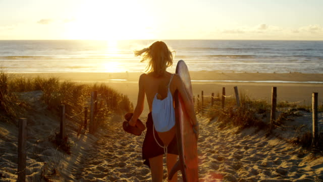 beautiful young woman in a swimsuit holding surfboard walks on the beach towards the sea. sun shines  on this gorgeous girl. sea is visible. - active lifestyle stock videos and b-roll footage