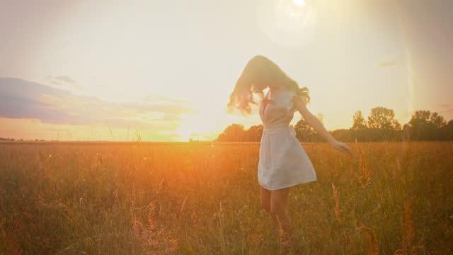 slo mo vacker ung kvinna i en vit klänning som snurrar i gräset vid solnedgången - klänning bildbanksvideor och videomaterial från bakom kulisserna