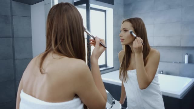 beautiful young woman in bath towel using cosmetic brush in front of mirror beautiful young woman in bath towel using cosmetic brush in front of mirror wearing a towel stock videos & royalty-free footage