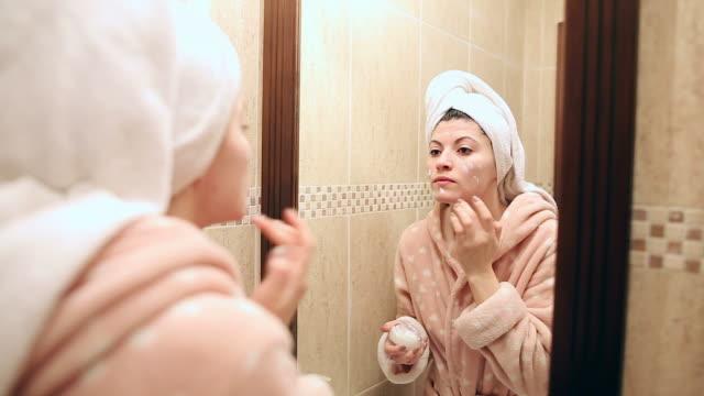 Beautiful young woman in bathroom applying moisturizer. video