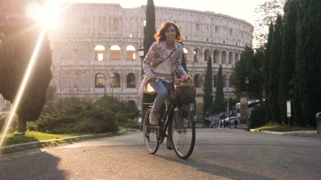 コッレ オッピオ公正面ステディカム ドリーに麦藁帽と木幸せな魅力的な女の子観光夕暮れ時ローマのコロッセオの前で自転車に乗ってカラフルなファッションで美しい若い女性 - 記念建造物点の映像素材/bロール