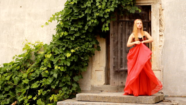 Beautiful young woman in fashion red dress posing video