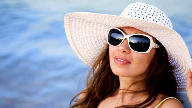 beautiful young woman in glasses sunbathing on the beach against the sea video
