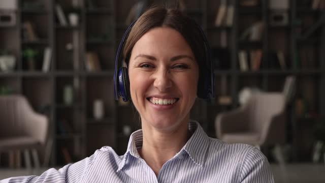 ビデオ通話を保持しているヘッドフォンで美しい若い女性。 - 人里離れた点の映像素材/bロール